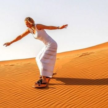 Women Sand Boarding in Desert